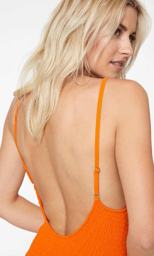 Oranžové jednodílné plavky s odhalenými zády
